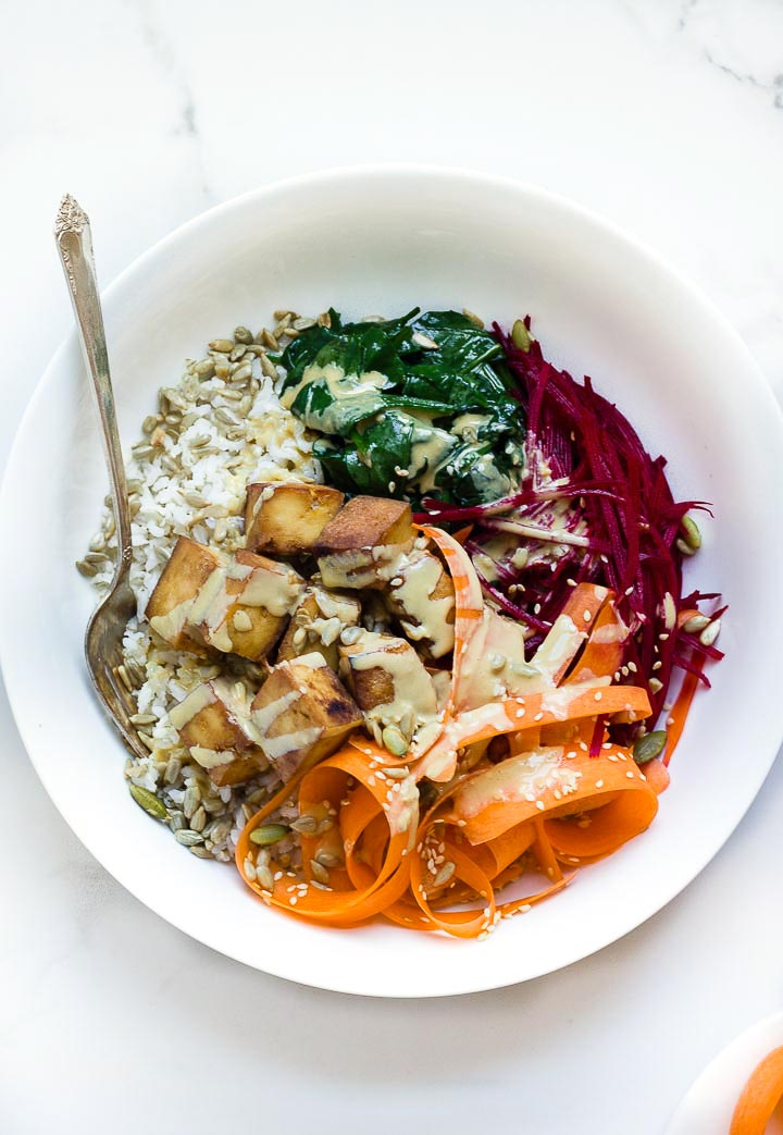 Glory bowl salad with brown rice, crispy tofu, carrots, beets, wilted spinach, toasted seeds and a delicious tahini dressing. Vegan and gluten free.