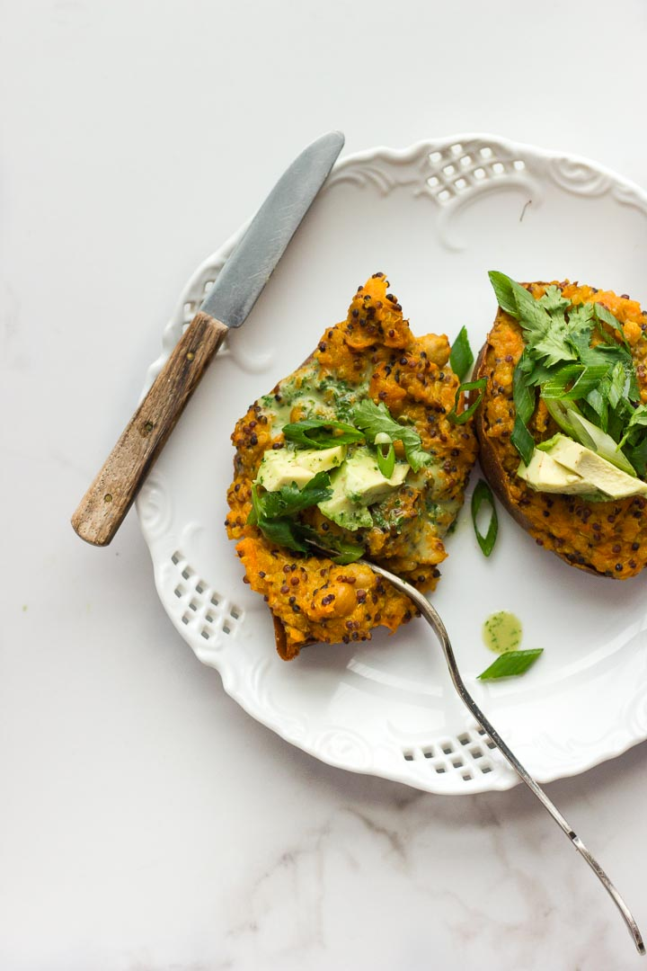 Vegan stuffed sweet potatoes with coconut curried quinoa, chickpeas and avocado cilantro sauce. Fully loaded with flavour. Gluten free.