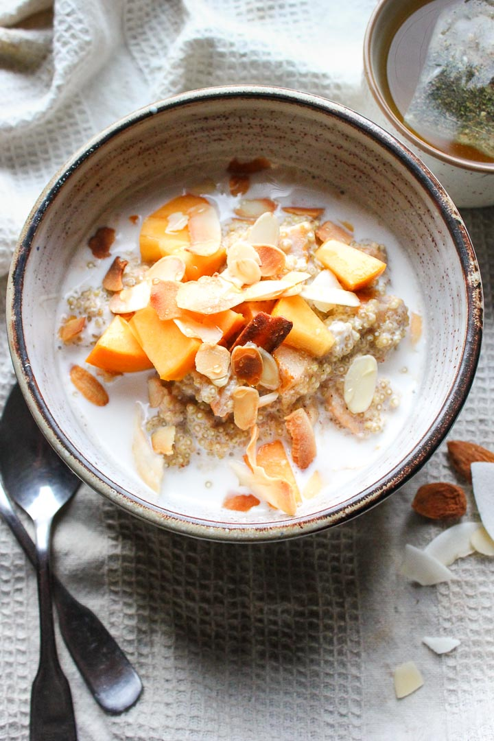 Creamy quinoa porridge bowl with almond milk, persimmons and toasted coconut. A quick and easy gluten free vegan breakfast!