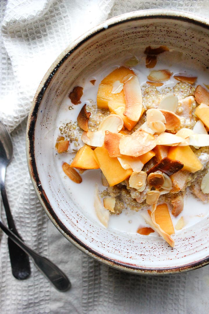 Creamy quinoa porridge with almond milk, persimmons and toasted coconut. A quick and easy gluten free vegan breakfast!