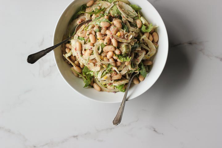 Shaved fennel white bean salad with an herby olive vinaigrette and lots of lemon. Vegan and gluten free. A simple and refreshing summer salad.