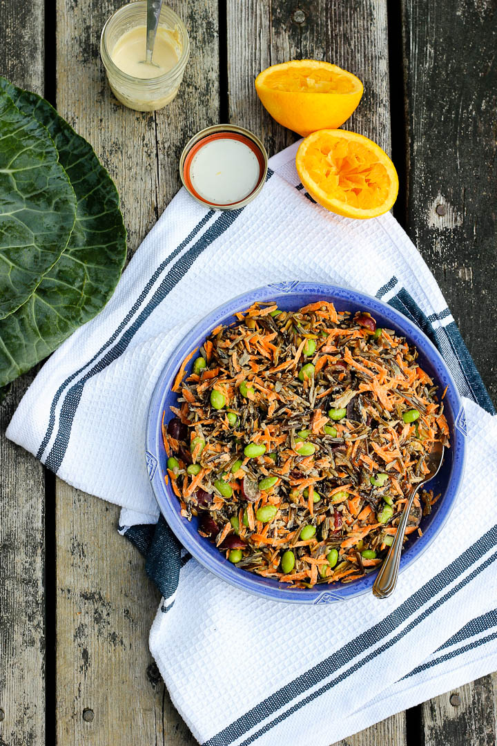 Collard wraps with wild rice salad + orange tahini dressing. Filled with edamame, grapes + carrots. Vegan + gluten free. Serves 6.