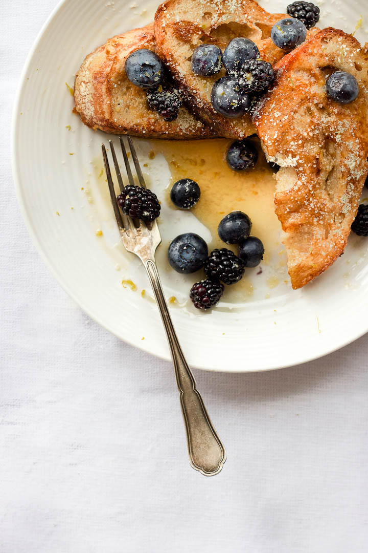 Vegan french toast made with almond milk and flavored with vanilla and cardamom. Summer breakfast done right with fresh berries