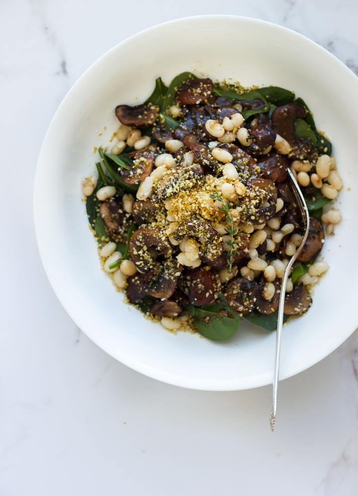Warm Balsamic Mushroom Salad with Pine Nut Parmesan from The First Mess Cookbook. Loaded with spinach and navy beans. Vegan and Gluten Free.