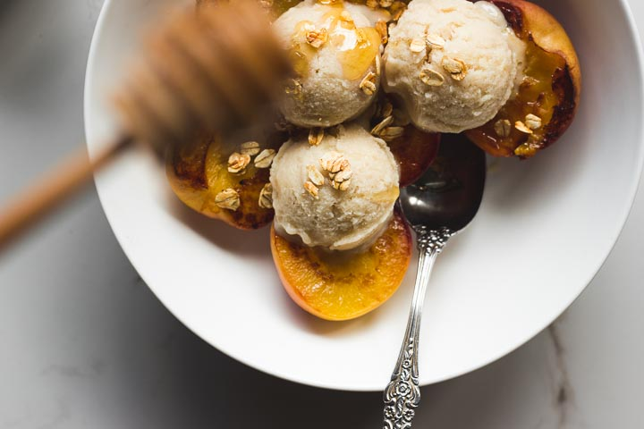 Easy, creamy vegan oat milk ice cream made with oats, vanilla and honey. Served with grilled peaches and honey toasted oats.
