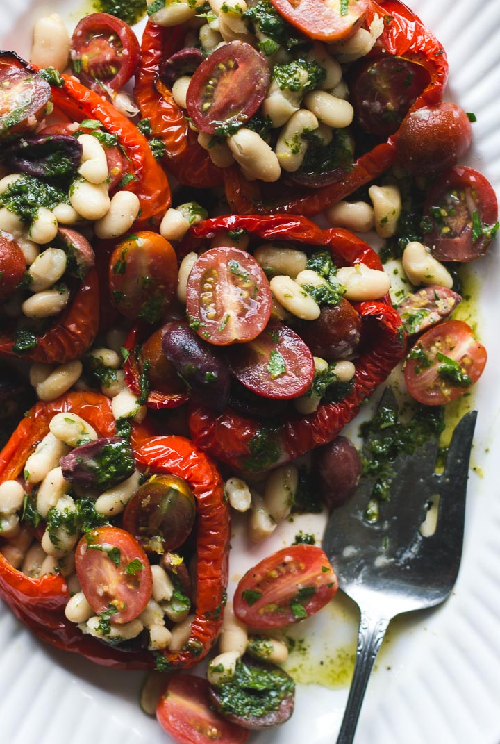Stuffed roasted red peppers with cherry tomatoes, white beans and olives. Covered in a basil dressing. Vegan and gluten free.